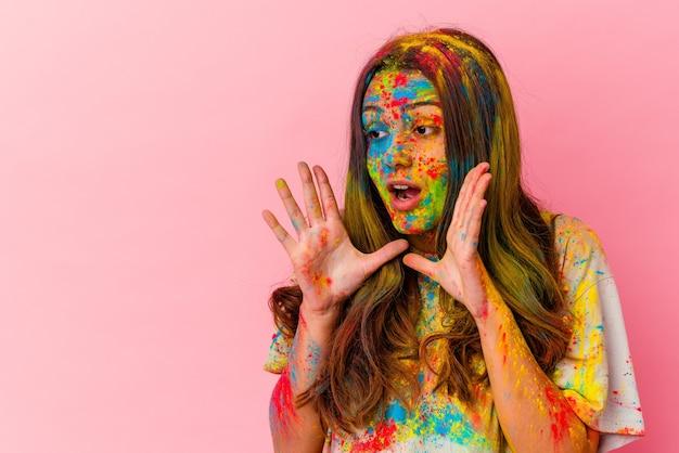 Jeune femme célébrant la fête sacrée isolée sur un mur blanc crie fort, garde les yeux ouverts et les mains tendues