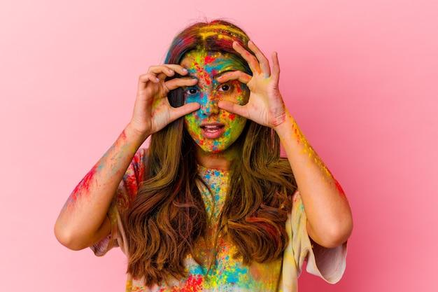 Jeune femme célébrant la fête sacrée isolée sur un mur blanc en gardant les yeux ouverts pour trouver une opportunité de succès
