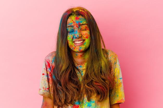 Jeune femme célébrant la fête sacrée isolée sur un mur blanc rit et ferme les yeux, se sent détendue et heureuse