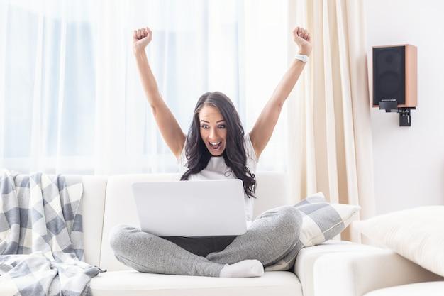 Jeune femme célébrant gagner une loterie en ligne à la maison avec ses bras levés et une expression de visage joyeux.