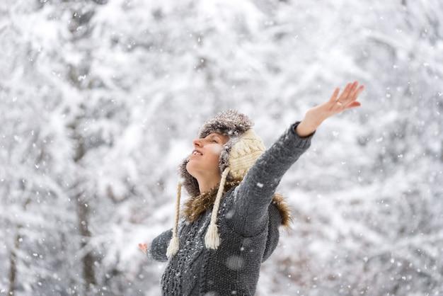 Jeune femme célébrant l'hiver debout à l'extérieur dans un jardin d'hiver dans la neige qui tombe avec ses bras écartés.