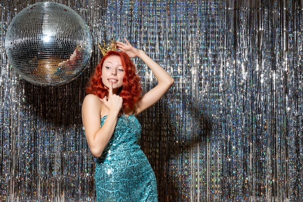 Jeune femme célébrant le nouvel an avec couronne sur des rideaux lumineux