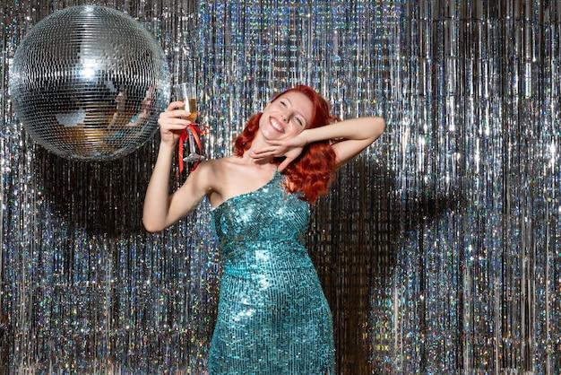 Jeune femme célébrant le nouvel an en fête avec boule disco sur lumineux