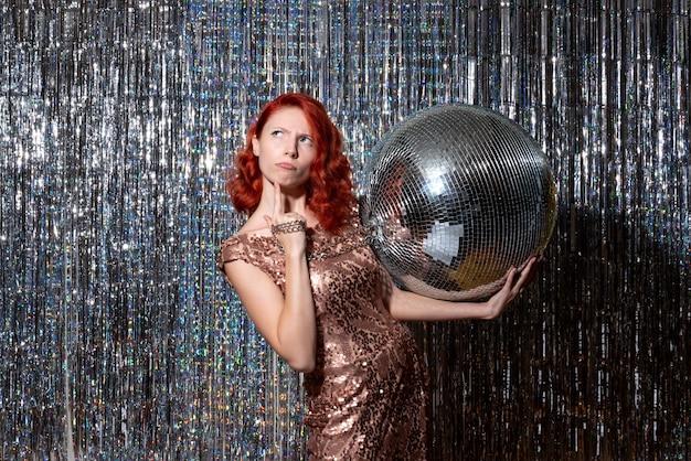Jeune femme célébrant le nouvel an en fête tenant une boule disco sur des rideaux lumineux rideaux