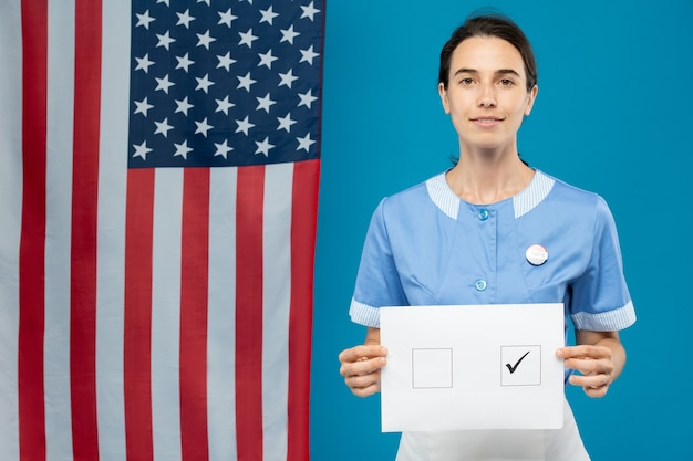 Jeune femme de chambre brune en uniforme bleu vous montrant son bulletin de vote avec coche dans l'un des carrés en se tenant debout contre le drapeau américain