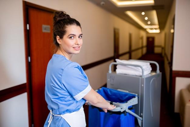 Jeune femme de chambre brune en uniforme vous regarde tout en poussant le chariot le long du couloir de l'hôtel le matin