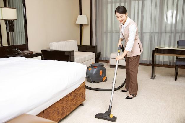 Jeune femme de chambre de l'hôtel nettoyage des chambres d'hôtel