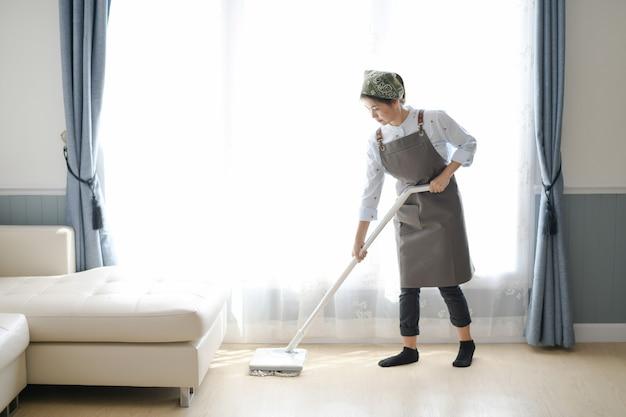 Une jeune femme de chambre nettoie la maison avec une vadrouille il y a une toile de fond de cuisine