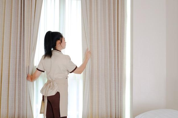 Jeune femme de chambre ouvrant les rideaux dans la chambre d'hôtel