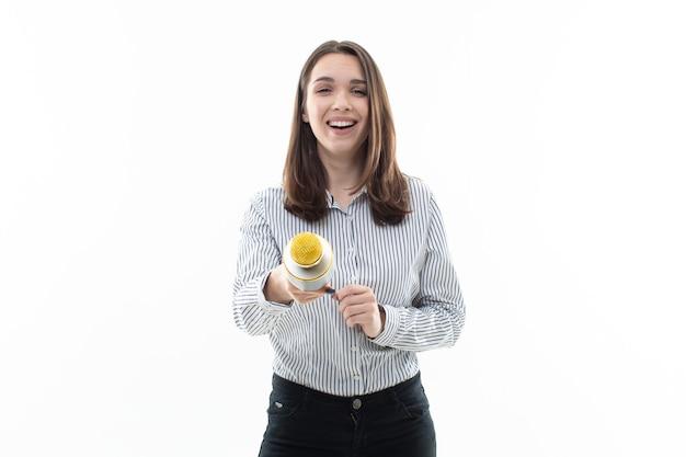 Jeune femme chante dans un microphone sur fond blanc