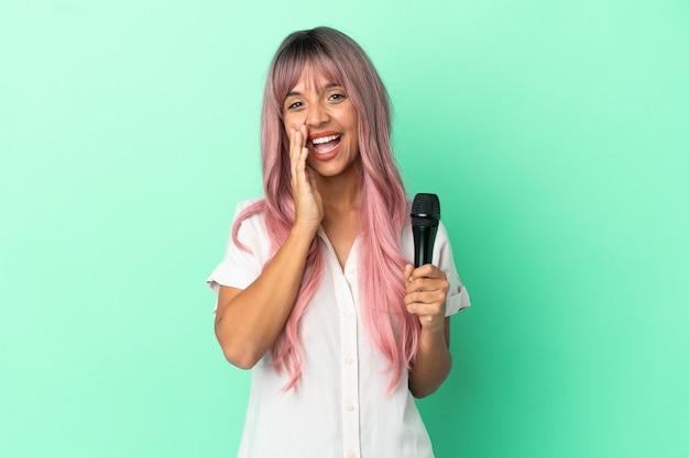 Jeune femme chanteuse métisse aux cheveux roses isolée sur fond vert criant avec la bouche grande ouverte