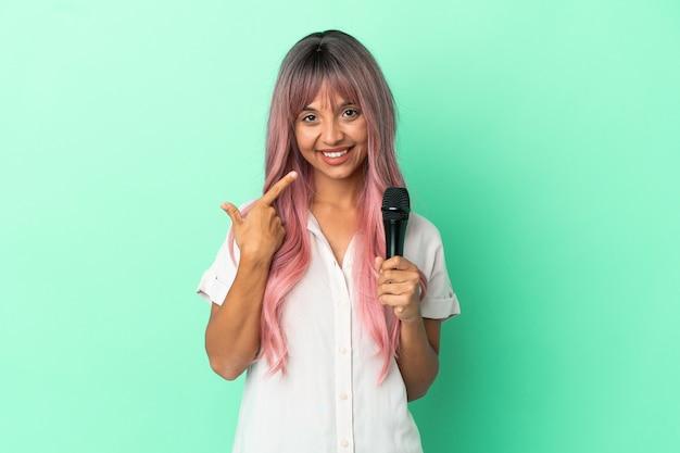 Jeune femme chanteuse métisse aux cheveux roses isolée sur fond vert donnant un geste du pouce vers le haut