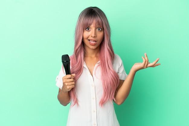 Jeune femme chanteuse métisse aux cheveux roses isolée sur fond vert avec une expression faciale choquée