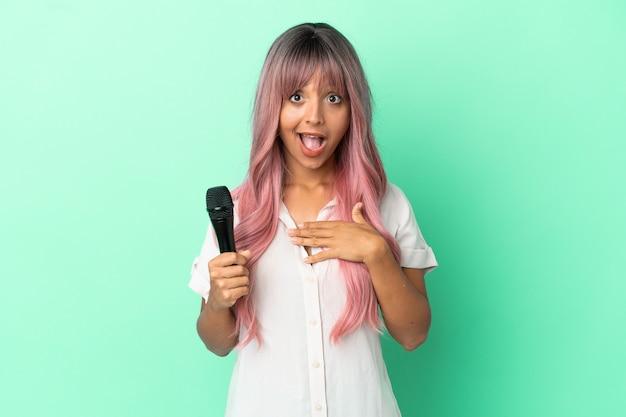 Jeune femme chanteuse métisse aux cheveux roses isolée sur fond vert avec une expression faciale surprise