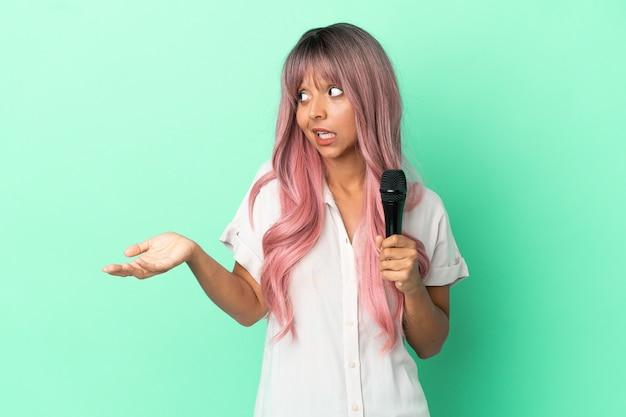 Jeune femme chanteuse métisse aux cheveux roses isolée sur fond vert avec une expression surprise en regardant de côté