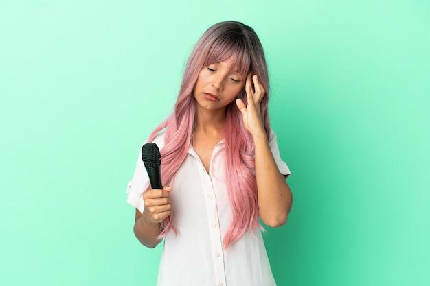 Jeune femme chanteuse métisse aux cheveux roses isolée sur fond vert avec maux de tête