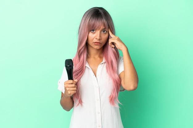 Jeune femme chanteuse métisse aux cheveux roses isolée sur fond vert en pensant à une idée