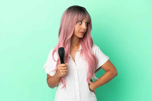 Jeune femme chanteuse métisse aux cheveux roses isolée sur fond vert regardant sur le côté