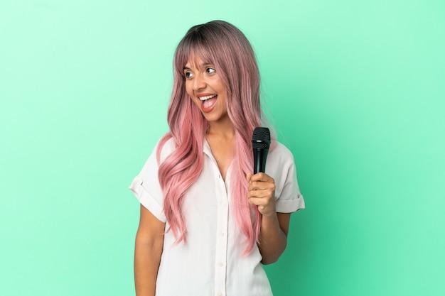 Jeune femme chanteuse métisse aux cheveux roses isolée sur fond vert en riant en position latérale