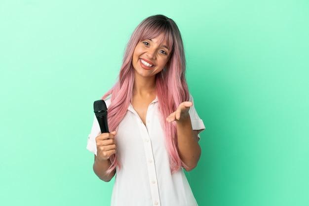 Jeune femme chanteuse métisse aux cheveux roses isolée sur fond vert se serrant la main pour conclure une bonne affaire