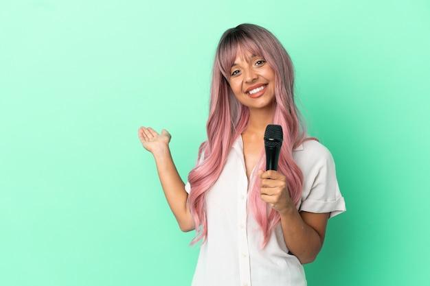 Jeune femme chanteuse métisse aux cheveux roses isolée sur fond vert tendant les mains sur le côté pour inviter à venir