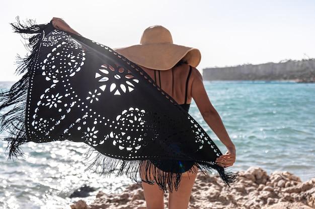 Une jeune femme avec un chapeau et une cape se repose près de la mer.
