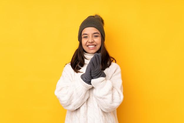 Jeune femme, à, chapeau hiver, sur, isolé, mur jaune, applaudir, après, présentation, dans, a, conférence