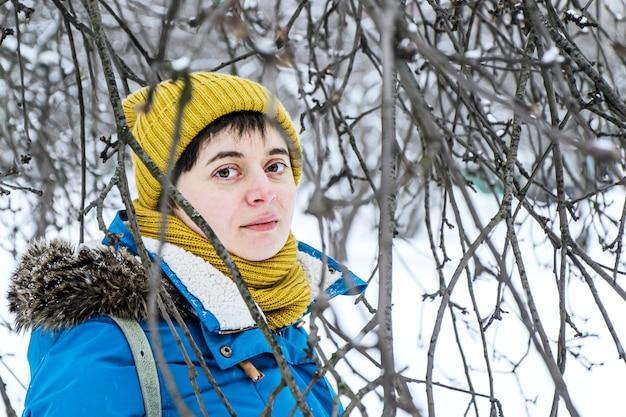 Jeune femme en chapeau d'hiver lumineux et veste parmi les branches d'arbres dans le parc d'hiver.
