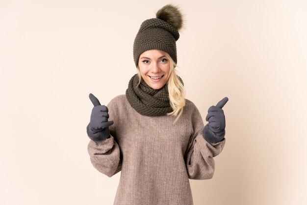 Jeune femme, à, chapeau hiver, sur, mur isolé, donner, a, pouces haut, geste