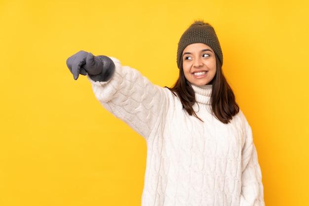 Jeune femme, à, chapeau hiver, sur, mur jaune, donner, a, pouce haut, geste