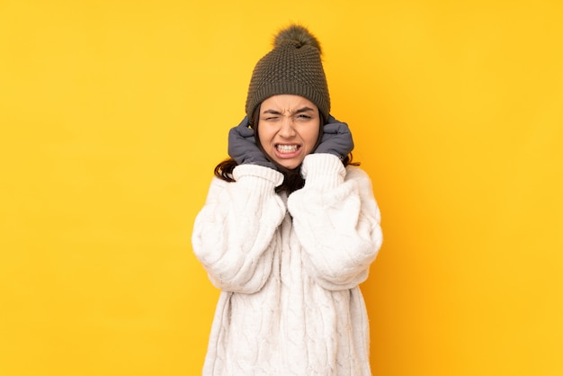 Jeune femme avec chapeau d'hiver sur le mur jaune frustré et couvrant les oreilles