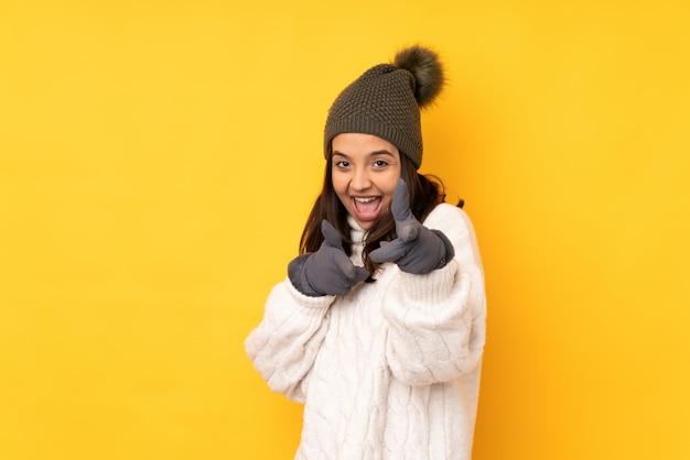 Jeune femme avec un chapeau d'hiver sur un mur jaune isolé pointant vers l'avant et souriant