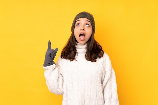 Jeune femme avec un chapeau d'hiver sur un mur jaune isolé pointant vers le haut et surpris