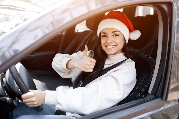 Jeune femme avec chapeau de père noël au volant de sa voiture
