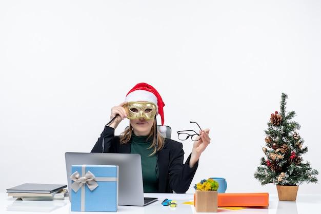 Jeune femme avec chapeau de père noël tenant des lunettes et portant un masque assis à une table avec un arbre de noël et un cadeau