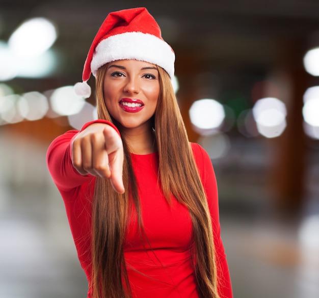 Jeune femme avec chapeau de santa, pointage, vous