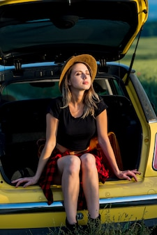 Jeune femme avec chapeau se trouve dans le coffre de la voiture en campagne