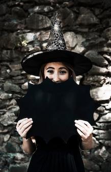 Jeune femme en chapeau de sorcier fermant la bouche avec une décoration d'halloween