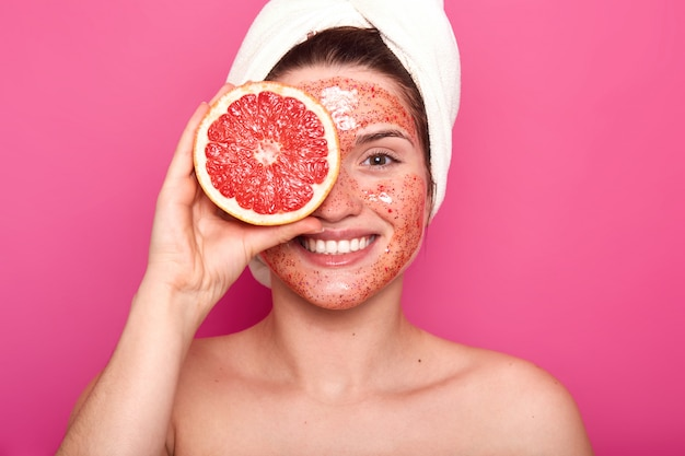 Une jeune femme charismatique émotionnelle avec un beau sourire sur son visage passe du temps à faire des procédures de beauté, rend sa peau fraîche et propre, tient la moitié du pamplemousse avec une serviette blanche sur la tête.