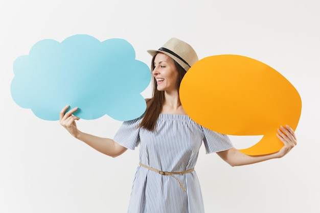 Jeune femme charmante élégante et tendre en robe bleue, chapeau avec un nuage de dites vide vide, bulles isolées sur fond blanc. les gens émotions sincères, concept de style de vie. espace publicitaire. espace de copie