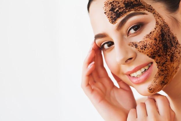 Jeune femme charmante fait un masque au charbon noir sur son visage