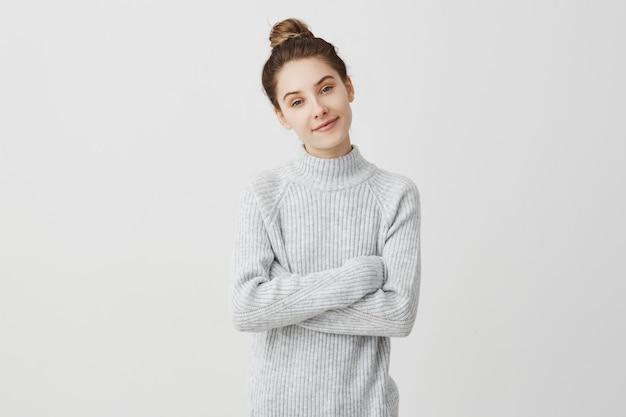 Jeune femme charmante en gris décontracté.