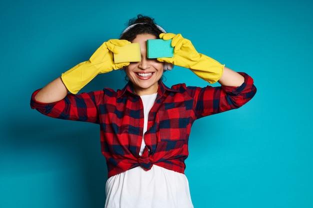 Jeune femme charmante posant à la caméra sur un bleu avec des éponges couvrant ses yeux et souriant avec un sourire à pleines dents