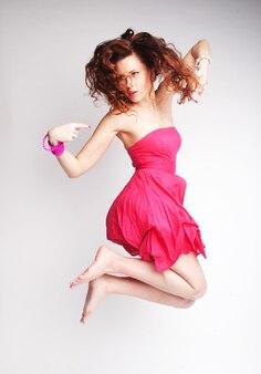 Jeune femme charmante en robe rose sautant par-dessus le mur gris
