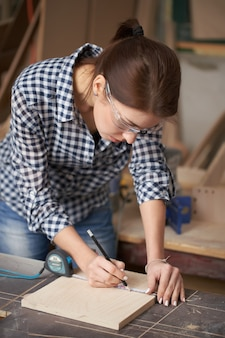 Jeune femme charpentier dans des verres avec ruban à mesurer et tableau noir en atelier