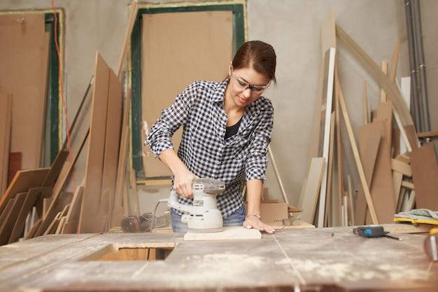 Jeune femme charpentier travaillant avec une scie à chantourner en atelier