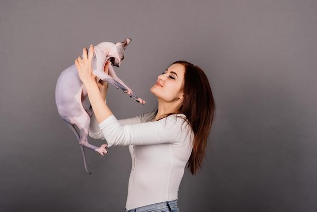 Jeune femme avec chat sphynx canadien dans un studio, fond gris