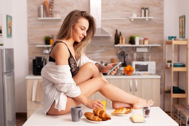 Jeune femme chaude assise sur la table de la cuisine portant de la lingerie sexy parcourant sur smartphone. femme séduisante avec des tatouages utilisant un téléphone portant des sous-vêtements temporaires le matin.