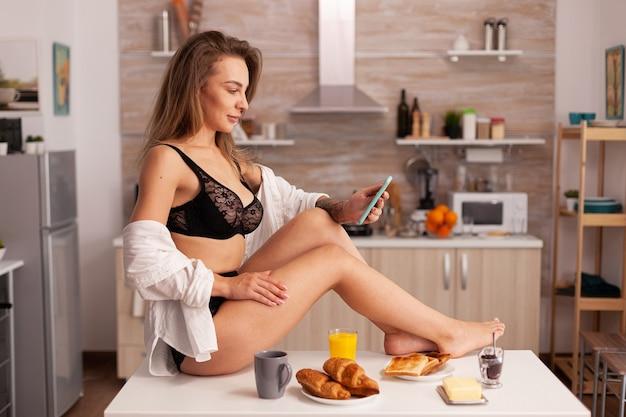 Jeune femme chaude assise sur la table de la cuisine portant de la lingerie sexy parcourant sur smartphone femme séduisante...