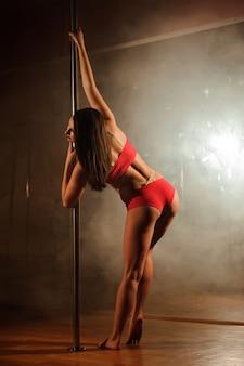 Jeune femme chaude en lingerie sexy effectue une pole dance sensuelle.